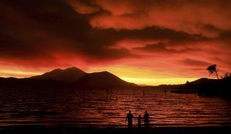 Evacuees from Lucerne, from left, Ken Bennett with Ember Reynolds, 8, and Lisa Reynolds watch the sunset as smoke from the Ranch Fire rises into the sky at Austin Park Beach in California's Clearlake with Mount Konocti in the background. (Kent Porter/The Press Democrat via AP)