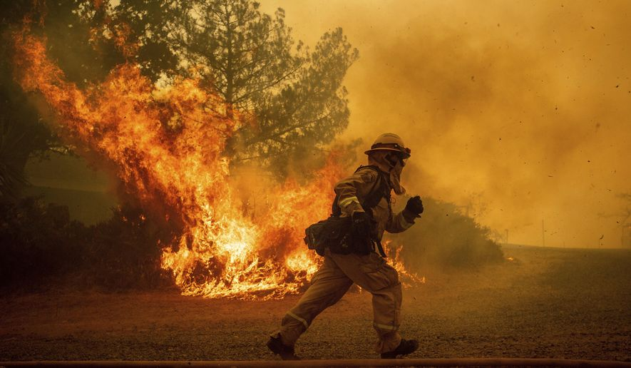 In this Tuesday, July 31, 2018, file photo, a firefighter runs while trying to save a home as a wildfire tears through Lakeport, Calif. The residence eventually burned. Authorities say a rapidly expanding Northern California wildfire burning over an area the size of Los Angeles has become the state's largest blaze in recorded history. It's the second year in a row that California has recorded the state's largest wildfire. (AP Photo/Noah Berger, File)