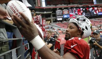 Arizona Cardinals running back David Johnson gives autographs to fans after an NFL football practice Saturday, Aug. 4, 2018, in Glendale, Ariz. (AP Photo/Ross D. Franklin)