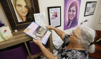 """In this Monday, Aug. 6, 2018 photo, Susan Bro, mother of Heather Heyer, who was killed during the Unite the Right rally last year, looks over memorabilia in her office in Charlottesville, Va. """"I just would like people to focus on the anniversary, not on Heather, but on the issues that she died for, Black Lives Matter, overpolicing, affordable housing, for more truth and the telling of the history of Charlottesville, and to focus on where they need to go as a community,"""" Bro said. (AP Photo/Steve Helber)"""