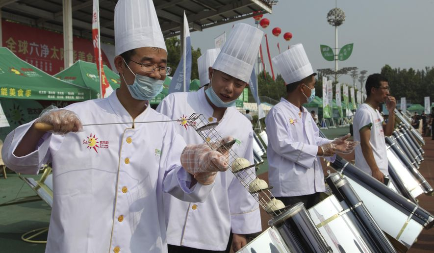 In this photo taken Thursday, Aug. 2, 2018, chefs prepare to cook buns in a solar cooker that using a metal and glass vacuum tube heated by mirrors curved to capture the sun's heat in Dezhou in the eastern Shandong province in China. Two dozen chefs with white aprons and hats cooked soups, baked buns, potatoes, and boiled rice at a festival to demonstrate the potential of solar cookers that organizers claim can help reduce climate-changing greenhouse gas emissions. (AP Photo/Fu Ting)