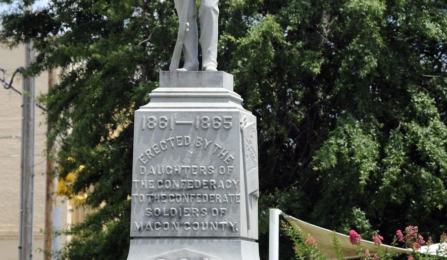 ADVANCE FOR THURSDAY AUG. 9, 2018--A Confederate monument dedicated in 1909 stands in the middle of the square in Tuskegee, Ala., on Thursday, June 28, 2018. Demonstrators once tried to topple the monument and it has been the target of vandals. Yet a Confederate heritage group owns the land, and the memorial has survived generations in a mostly black city known as a landmark of minority education and empowerment. Black graffiti from a vandalism incident that occurred last year is still visible on the base. (AP Photo/Jay Reeves)