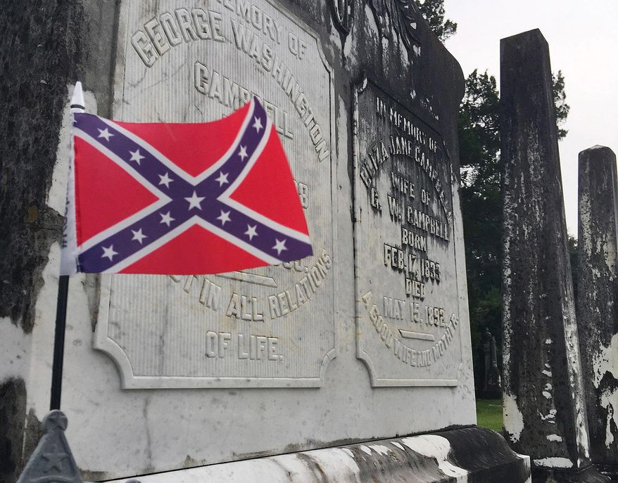 A small Confederate battle flag waves at the grave of a Confederate veteran in a cemetery in Tuskegee, Ala., on Tuesday, July 31, 2018. (AP Photo/Jay Reeves)