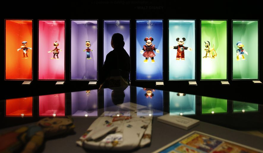 "FILE- In this Nov. 16, 2017, file photo, a visitor walks past a display of Disney characters inside an exhibition entitled ""Mexico and Walt Disney: A Magical Encounter,"" at the Cineteca Nacional, Mexico's film archive, in Mexico City. The Walt Disney Co. reports earnings Tuesday, Aug. 7, 2018. (AP Photo/Rebecca Blackwell, File)"
