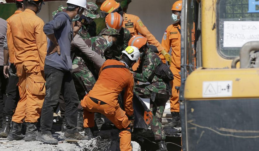 Rescuers carry the body of an earthquake victim recovered from the collapsed Jabal Nur Mosque in North Lombok, Indonesia, Tuesday, Aug. 7, 2018. The north of Lombok was devastated by the powerful quake that struck Sunday night, damaging thousands of buildings and killing a large number of people. Rescuers were still struggling to reach all of the affected areas and authorities expect the death toll to rise. (AP Photo/Tatan Syuflana)