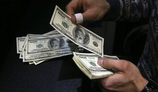 """FILE - In this Dec. 26, 2016 file photo, a currency exchange bureau owner counts U.S. dollars in downtown Tehran, Iran. Iran's Central Bank has allowed money exchange offices across the country to resume work after a ban imposed in March 2018 amid the country's economic troubles. The bank's governor, Abdolnasser Hemmati, told sate TV late on Sunday, Aug 5, 2018, that """"money exchangers are allowed to sell and buy foreign currencies."""" (AP Photo/Vahid Salemi, File)"""