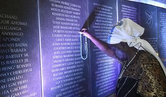 80-year old Margaret Achieng places a rosary on her daughters name Doreen Aluoch at plague with the names of victims of the August 7, 1998 US embassy bombing at the Kenya's capital Nairobi during the 20th commemoration at the memorial park, Nairobi, Kenya, Tuesday, Aug. 7, 2018. (AP Photo/Andrew Kasuku)