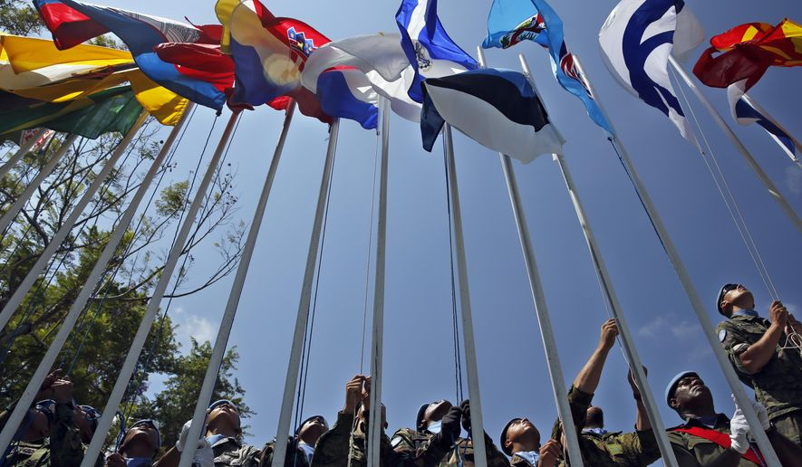 U.N. peacekeepers raise the flags of their country during a ceremony to mark the transfer of authority between the outgoing and the newly appointed head of the mission at the UNIFIL headquarters in the southern Lebanese town of Naqoura, Lebanon, Tuesday, Aug. 7, 2018. (AP Photo/Bilal Hussein)