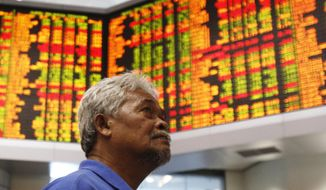 In this  July 26, 2018, photo, an investor stands in front of private stock trading boards at a private stock market gallery in Kuala Lumpur, Malaysia. Asian stock markets followed Wall Street higher on Tuesday, Aug. 7, 2018, as strong corporate profits helped to defuse fears over U.S.-China trade tensions. (AP Photo/Yam G-Jun)
