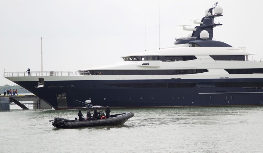 Malaysia's marine police on their security boat watch luxury yacht Equanimity, allegedly bought with money stolen from the multibillion-dollar looting of a state investment fund, arriving at Port Klang in Klang, Malaysia, Tuesday, Aug. 7, 2018. The $250 million Equanimity, seized by Indonesia off Bali in February in cooperation with the U.S. FBI, was handed over to Malaysian authorities on Monday at the Indonesian island of Batam near Singapore. (AP Photo/Yam G-Jun)
