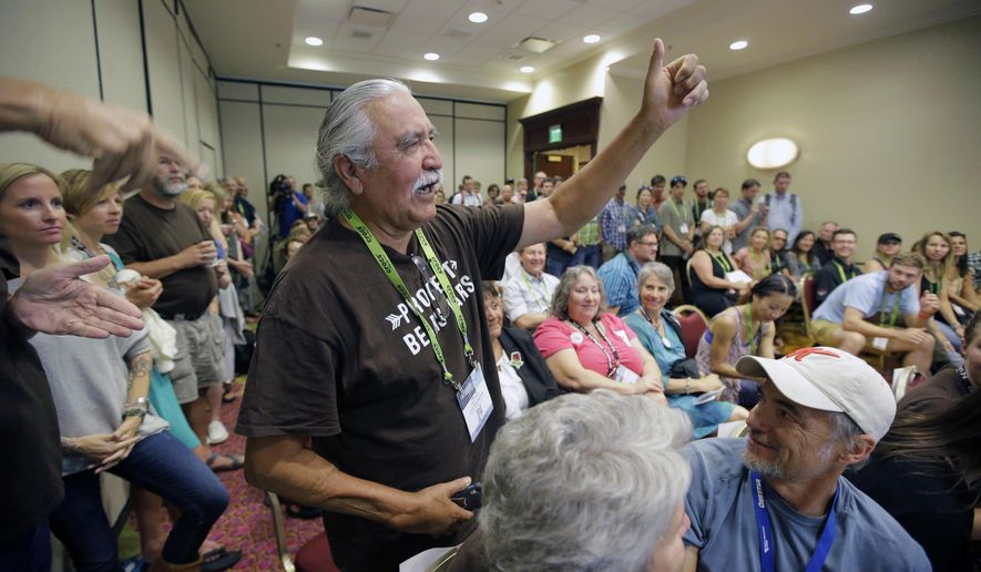 FILE - This Aug. 4, 2016, file photo, Willie Grayeyes raises his hand as he is recognized during a news conference, in Salt Lake City. A Navajo man will be put back on the ballot for county commission after a judge sided with him in his lawsuit against a Utah county that disqualified him in the first election since a judge ruled local voting districts were illegally drawn based on race. Leonard Gorman of the Navajo Nation Human Rights Commission said U.S. District Judge David Nuffer ordered San Juan County to put Willie Grayeyes back on the ballot during a hearing Tuesday in Moab that Gorman attended. (AP Photo/Rick Bowmer, File)
