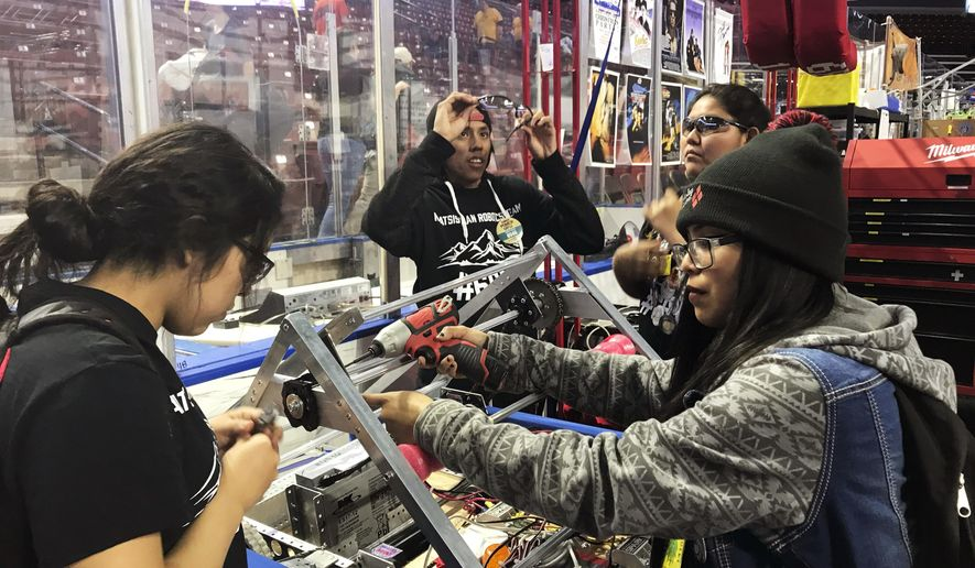 This March 3, 2018 photo provided by Heather Anderson shows, from left, Navajo Mountain High School students Nahida Smith, Myra King and Breana Bitsinne compete in a Utah regional robotics competition in West Valley City, Utah.  The team from a remote town in southern Utah is now headed to an international robotics competition Aug. 14 in Mexico City, Mexico.   They were invited to compete in the First Global Challenge, which will draw teams from 190 countries to create robots capable of feeding power plants and building environmentally efficient transmission networks.  (Heather Anderson via AP)