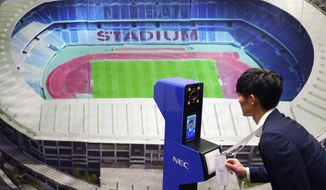 A staff demonstrates a new face recognition system used for the Tokyo 2020 Olympic and Paralympic Games during a press conference in Tokyo Tuesday, Aug. 7, 2018. The NeoFace technology developed by NEC Corp. will be used across the Olympics for the first time as Tokyo organizers work to keep security tight and efficient at dozens of venues during the 2020 Games. (AP Photo/Eugene Hoshiko)