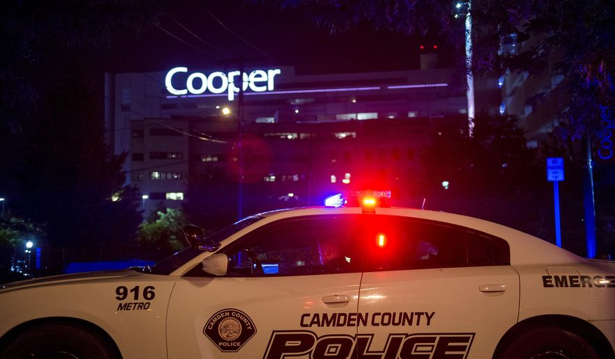 An officer is posted by Copper hospital following a shooting that left two detectives wounded in Camden, N.J., Tuesday, Aug. 7, 2018. Camden County Police Chief J. Scott Thomson said at least one suspect opened fire on the plainclothes detectives Tuesday night in Camden, located just across the Delaware River from Philadelphia. (Joe Lamberti/Camden Courier-Post via AP)