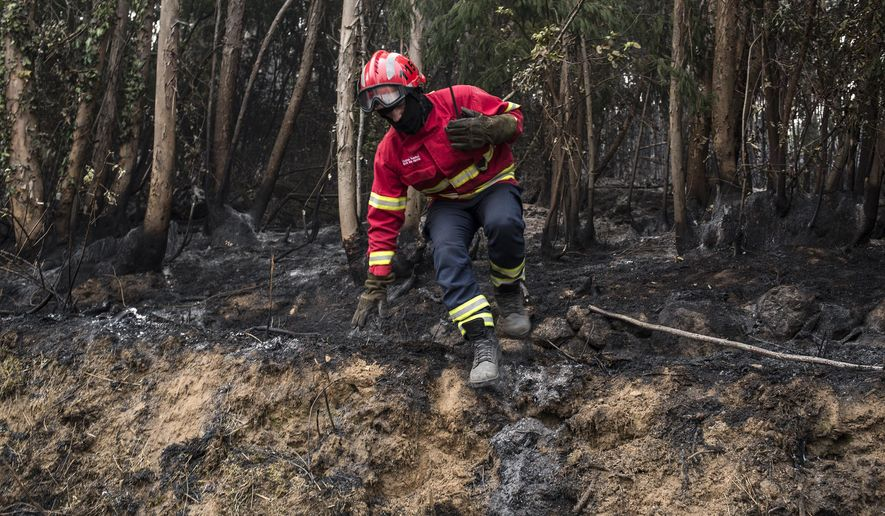 A firefighter jumps off a small mound while working on a fire near the village of Monchique, in southern Portugal's Algarve region, Monday, Aug. 6, 2018. Emergency services in Portugal say they are still fighting a major wildfire on the south coast that threatened to engulf a hillside town overnight. (AP Photo/Javier Fergo)