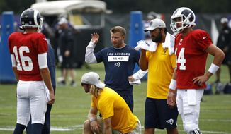 Los Angeles Rams head coach Sean McVay, center, speaks with quarterback Jared Goff (16) during a joint NFL football training camp practice at the Baltimore Raven's headquarters, Tuesday, Aug. 7, 2018, in Owings Mills, Md. (AP Photo/Patrick Semansky)