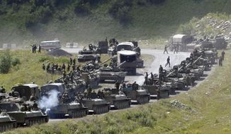 "In this file photo taken on Saturday, Aug. 9, 2008, a column of Russian armored vehicles seen on their way to the South Ossetian capital Tskhinvali somewhere in the Georgian breakaway region, South Ossetia, Georgia. The Russian military quickly routed the Georgian army during the August 2008 war. Russia's Prime Minister Dmitry Medvedev in an interview broadcast by Russian state television Tuesday Aug. 7, 2018, on the 10th anniversary of the Russia-Georgia war, issued a stern warning that incorporating Georgia into NATO could trigger a new ""horrible"" conflict. (AP Photo/Musa Sadulayev, File)"