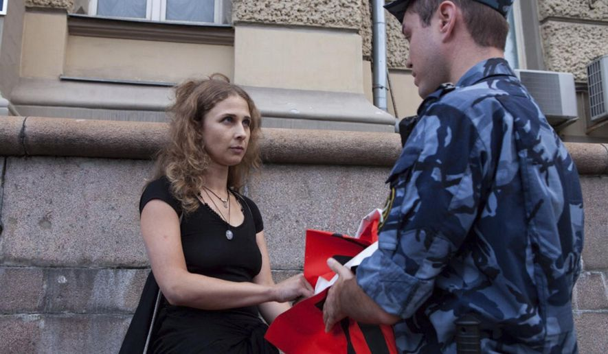 Russian activist of the feminist protest group Pussy Riot Maria Alekhina talks to a policeman as she holds a protest in front of the Federal Penitentiary building in Moscow, Russia, Tuesday, Aug. 7, 2018. Pussy Riot protest against torture in Russian prisons. (AP Photo/ Alexander Sofeev)