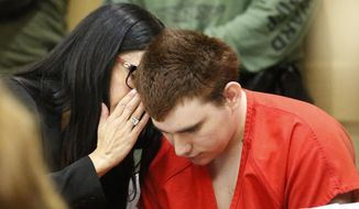 Assistant Public Defender Erin Veit, left, talks with school shooting suspect Nikolas Cruz sits in a Broward County courtroom for a hearing in Fort Lauderdale, Fla., Friday, Aug. 3, 2018. Attorneys for Cruz want a judge to prevent release of details of his education records to guarantee a fair trial. Cruz faces the death penalty if convicted of killing 17 people in the Valentine's Day attack at Marjory Stoneman Douglas High School. (AP Photo/Wilfredo Lee, Pool)