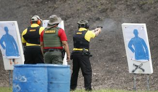 """In this Monday, July 30, 2018 photo, a Broward Sheriff's Office (BSO) trainer, center, watches two Broward County Public Schools newly-hired armed guardians during firearms training at BSO's gun range at Markham Park in Sunrise, Fla. In August 2019, Holmes County [Fla.] Sheriff John Tate announced his department would offer classes for concealed-carry permit holders to train to be prepared to be """"a good guy with a gun"""" in an active-shooter scenario. (AP Photo/Wilfredo Lee) **FILE***"""