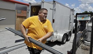 In this Monday, Aug. 6, 2018, photo, Troy Knutson loads supplies into a storage facility in Bradenton, Fla. Data shows that small businesses are hiring less, despite the strong economy, partly because they are losing employees to bigger firms.(AP Photo/Chris O'Meara)