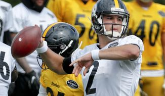 Pittsburgh Steelers quarterback Mason Rudolph (2) looks to pass as defensive back Nat Berhe pressures in a goal-line drill at NFL football training camp in Latrobe, Pa., Tuesday, Aug. 7, 2018. Rookie quarterback Rudolph gets a chance to show how far he's come since being drafted in April when the Steelers open the preseason in Philadelphia on Thursday. Rudolph is in a fight for a backup spot behind Ben Roethlisberger.(AP Photo/Keith Srakocic)