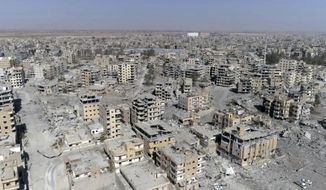 """FILE -- In this Thursday, Oct. 19, 2017 file photo, a frame grab made from drone video shows damaged buildings in Raqqa, Syria. Amnesty International, an international rights group, urged the U.S.-led military coalition battling the Islamic State group to investigate airstrikes that killed civilians in the campaign to liberate the Syrian city of Raqqa from the extremists. Amnesty said Tuesday, Aug. 7, 2018,  that the U.S.-coalition's admission last month that it killed 78 more civilians than previously reported in the 2017 assault on Raqqa was just the """"tip of the iceberg."""" (AP Photo/Gabriel Chaim, File)"""