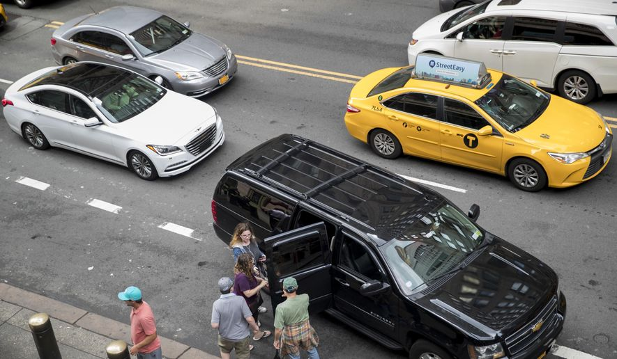 In this Wednesday, Aug. 1, 2018 photo, traffic on 42nd Street makes it's way around a ride-hailing car picking up passengers outside Grand Central Terminal in New York. Once synonymous with New York City, yellow taxis have been supplanted by an army of black cars that pick up riders through the Uber, Lyft and other apps. The rise in the number of ride-hail vehicles has been so dizzying that the New York City Council is pondering a series of legislative proposals to be voted on Wednesday, Aug. 8. (AP Photo/Mary Altaffer)