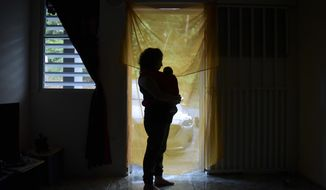 FILE - In this Friday, Dec. 16, 2016 file photo, Michelle Flandez stands in her home with her two-month-old son Inti Perez, who is diagnosed with microcephaly linked to the mosquito-borne Zika virus, in Bayamon, Puerto Rico. In the first long-term look at what happened to children of U.S. mothers who were infected with Zika during pregnancy, one in seven developed some kind of health problem _ranging from birth defects to conditions that became apparent only later. Health officials released the findings Tuesday, Aug. 7, 2018. (AP Photo/Carlos Giusti)