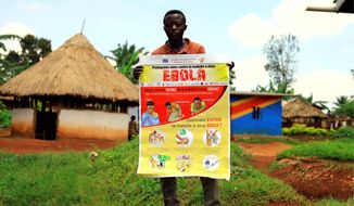 A man displays an Ebola information leaflet for residents on Wednesday in Mangina in the Democratic Republic of Congo, where the World Health Organization said responders plan to give an experimental vaccination shot to 40 front-line health workers. (ASSOCIATED PRESS)