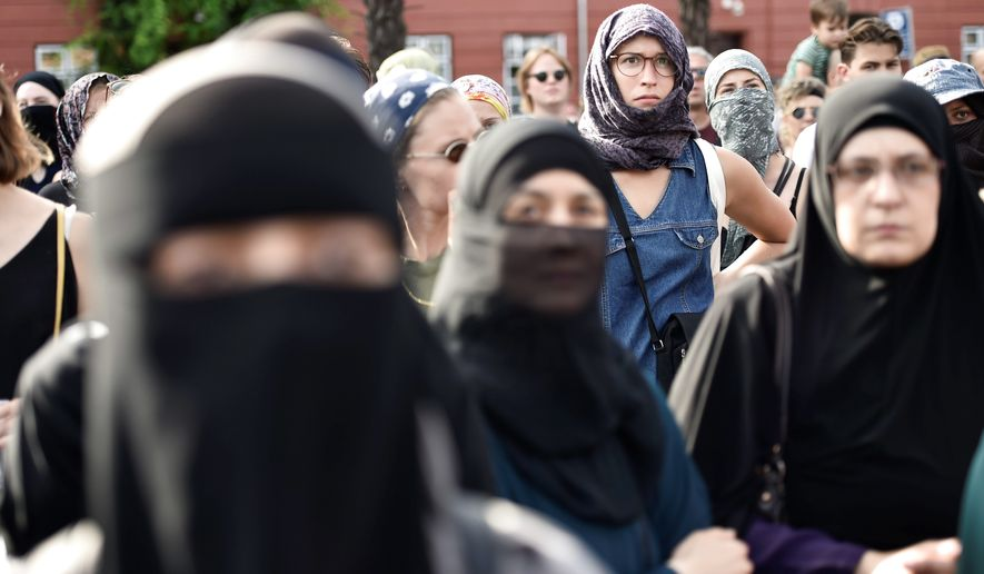 People demonstrate in Copenhagen, Denmark, Wednesday Aug. 1, 2018, as the new ban on garments covering the face is implemented. Supporters and opponents of a ban on garments covering the face, including Islamic veils such as the niqab or burqa, clashed verbally Wednesday as the law takes effect. (Mads Claus Rasmussen/Ritzau Scanpix via AP)