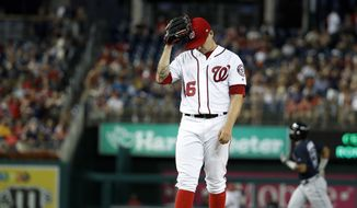 Washington Nationals starting pitcher Tommy Milone reacts as Atlanta Braves' Ronald Acuna Jr., back, rounds the bases on a two-run home run during the fourth inning of a baseball game at Nationals Park, Wednesday, Aug. 8, 2018, in Washington. (AP Photo/Alex Brandon)