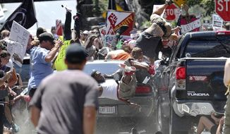 In this Aug. 12, 2017, file photo, people fly into the air as a vehicle drives into a group of protesters demonstrating against a white nationalist rally in Charlottesville, Va. Efforts to take down Americas monuments honoring slain Confederate soldiers and the generals who led them gained explosive momentum following the deadly violence a year ago in Charlottesville. The vehicle plowed into a crowd protesting a gathering of white supremacists whose stated goal was to protect a statue of Gen. Robert E. Lee. (Ryan M. Kelly/The Daily Progress via AP, File)