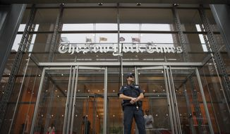 In this June 28, 2018, file photo, a police officer stands guard outside The New York Times building in New York. The New York Times Co. reports earnings Wednesday, Aug. 8. (AP Photo/Mary Altaffer, File) **FILE**