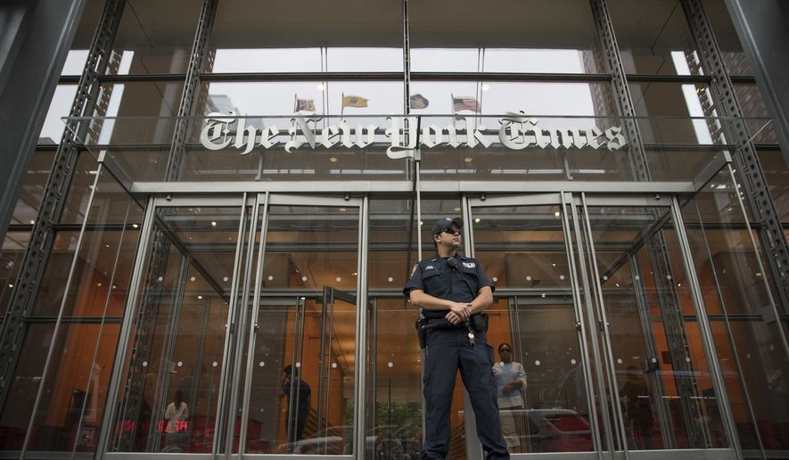 FILE- In this June 28, 2018, file photo, a police officer stands guard outside The New York Times building in New York. The New York Times Co. reports earnings Wednesday, Aug. 8. (AP Photo/Mary Altaffer, File)
