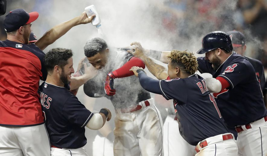 Cleveland Indians' Francisco Lindor, center, is welcomed by teammates after he hit a walk-off three-run home run against the Minnesota Twins in a baseball game Wednesday, Aug. 8, 2018, in Cleveland. The Indians won 5-2. (AP Photo/Tony Dejak)