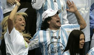 FILE - In this Dec. 2, 2006 file photo, Argentina's former soccer great Diego Maradona and his ex-wife Claudia Villafane, left, support their national team during the Davis Cup Final tennis match against Russia, in Moscow. An appeals court has ruled on Wednesday, Aug. 8, 2018, that Maradona can pursue a lawsuit against his ex-wife claiming she misappropriated some of his money to buy Florida real estate. (AP Photo/Ivan Sekretarev, File)