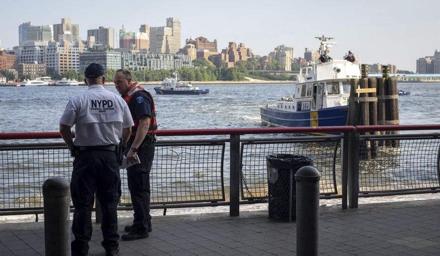 FILE - In this Aug. 5, 2018, file photo, authorities investigate the death of a baby boy who was found floating in the East River near the Brooklyn Bridge in Manhattan in New York. A Bronx father hopped a plane to Thailand after carrying his dead 7-month-old baby around New York City in a backpack and tossing the boy's body into the river and other tourist hotspots, police said Wednesday. (AP Photo/Robert Bumsted, File)