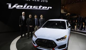 FILE- In this Jan. 15, 2018, file photo, from left, Albert Biermann, head of performance development for the Hyundai Motor Group, Chief Designer Peter Schreyer, President and CEO of Hyundai Motor America Kenny Lee and Hyundai Vice Chairman Moosik Kwan, stand next to the 2019 Veloster N model during the North American International Auto Show in Detroit. The N gets a bigger turbocharged engine good for up to 275 horsepower plus additional hardware upgrades. (AP Photo/Carlos Osorio, File)