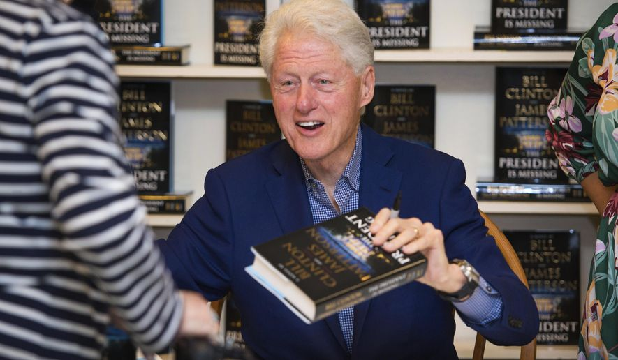 """FILE - In a June 28, 2018 file photo, President Bill Clinton holds a copy of """"The President is Missing"""" at Book Revue, in Huntington, NY. The book, co-written with James Patterson, has more than 1 million sales in North America. (Photo by Scott Roth/Invision/AP, File)"""