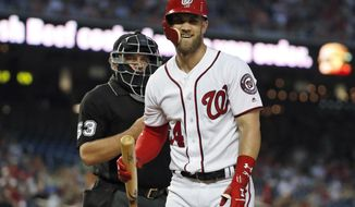 Washington Nationals' Bryce Harper laughs at a called third strike by home plate umpire Greg Gibson during the third inning of the team's baseball game against the Atlanta Braves at Nationals Park, Wednesday, Aug. 8, 2018, in Washington. (AP Photo/Alex Brandon)