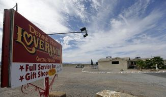 In this Oct. 14, 2015, file photo, a sign advertises Dennis Hof's Love Ranch brothel in Crystal, Nev. A proposed amendment for a Nye County ordinance would restrict the hours when legal prostitutes are permitted to leave licensed brothels, a policy change proposed say is meant to prevent unprotected sex but which sex workers complain infringes on their rights.  (AP Photo/Chris Carlson, File) **FILE**