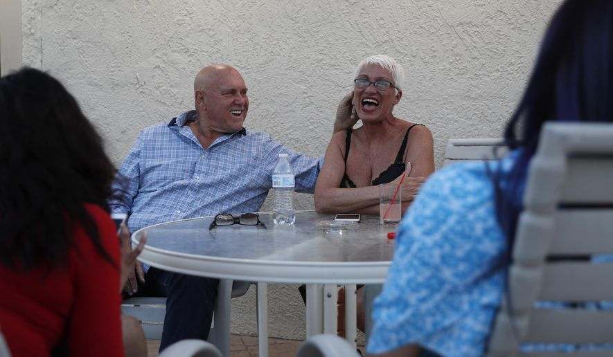 FILE - In this April 27, 2018, file photo, owner Dennis Hof, left, jokes with madam Sonja Bandolik at the Love Ranch brothel in Crystal, Nev. County officials in Nevada have yanked a brothel license from the state's most famous pimp who has fashioned himself as a Donald Trump-style candidate for Nevada's legislature. Officials in Southern Nevada's Nye County on Tuesday said Dennis Hof had failed to apply for a renewal and pay fees for his Love Ranch brothel in Crystal, about an hour's drive northwest of Las Vegas. (AP Photo/John Locher, File)