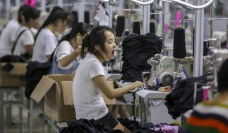 In this Thursday, Aug. 2, 2018, photo, a woman yawns at a factory making swimming suits in Jinjiang city in southeast China's Fujian province. China's exports accelerated in July, showing little impact from a U.S. tariff hike, while sales to the United States rose 13.3 percent over a year earlier. (Chinatopix via AP)