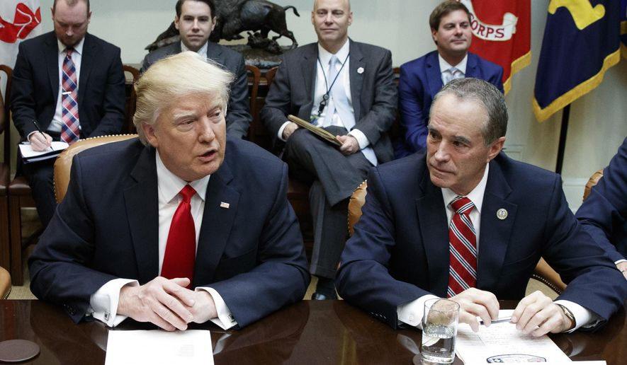 In this Feb. 16, 2017, file photo Republican U.S. Rep. Chris Collins of western New York state, right, sits next to President Donald Trump during a meeting with House Republicans in the Roosevelt Room of the White House in Washington. Collins was indicted on charges that he used inside information about a biotechnology company to make illicit stock trades. Collins' son and a family acquaintance were also charged. The charges were announced and the indictment unsealed on Wednesday, Aug. 8, 2018. (AP Photo/Evan Vucci, File)