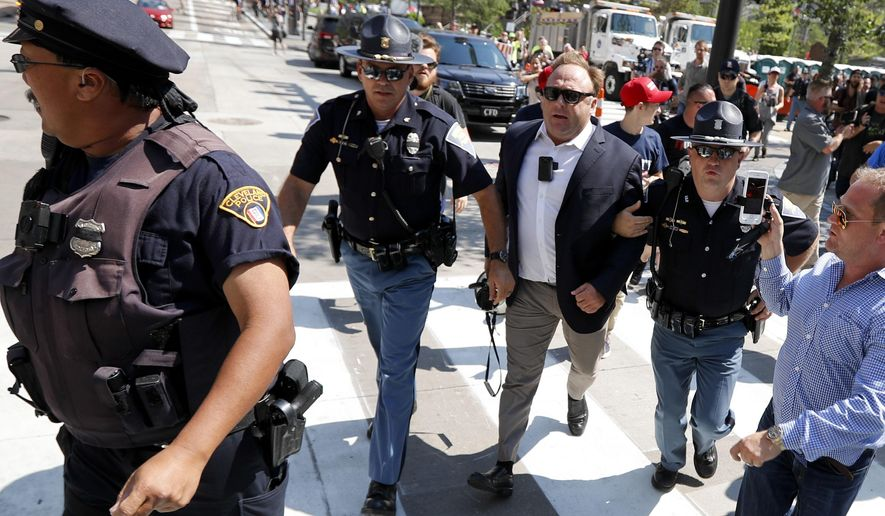 In this Tuesday, July 19, 2016, file photo, Alex Jones, center right, is escorted by police out of a crowd of protesters outside the Republican convention in Cleveland. (AP Photo/John Minchillo, File)