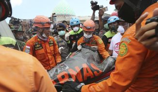 Emergency workers recover a body from the Jamiul Jamaah Mosque after it collapsed during an earthquake in Bangsal, North Lombok, Indonesia, Wednesday, Aug. 8, 2018. The north of Lombok was devastated by the powerful quake that struck Sunday night, damaging thousands of buildings and killing a large number of people. Rescuers were still struggling to reach all of the affected areas and authorities expect the death toll to rise. (AP Photo/Tatan Syuflana)