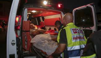 Injured person is taken to ambulance after a missile from Gaza Strip hit in the town of Sderot, Israel, Wednesday, Aug. 7, 2018. Sirens wailed in southern Israel warning of incoming projectiles from Gaza and Israeli media reported two people were lightly injured from shrapnel in the border town of Sderot. (AP photo/Yehuda Peretz)