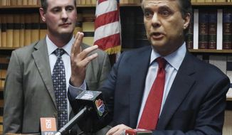 FILE - In this May 30, 2018, file photo, Kansas Gov. Jeff Colyer, right, answers a question from reporters as Lt. Gov. Tracey Mann, left, listens during a news conference in Topeka, Kan. Colyer and immigration hardliner Kris Kobach were virtually tied atop a seven-candidate field with nearly two-thirds of the precincts counted in the primary, late Tuesday, Aug. 7, 2018. (AP Photo/John Hanna, File)