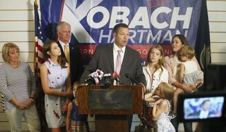 Secretary of State Kris Kobach, surrounded by his family and running mate Wink Hartman, talked to the media during a news conference at the Topeka Capitol Plaza hotel in Topeka, Kan., Wednesday, Aug. 8, 2018. (Thad Allton/The Topeka Capital-Journal via AP)